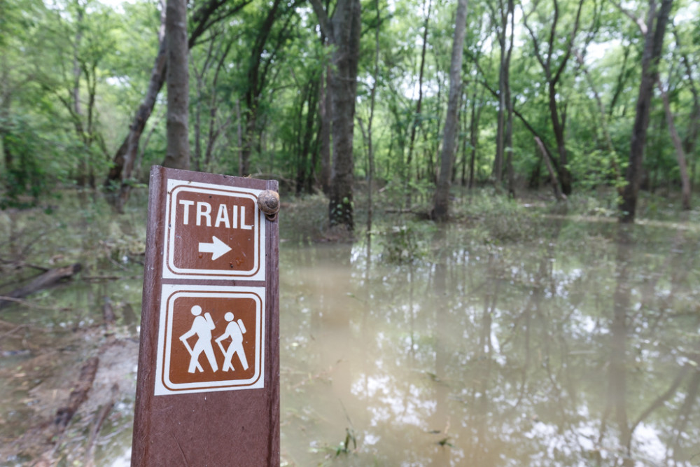 Trail sign with snail and flooded Buckeye Trail, Great Trinity Forest, Dallas, Texas, USA