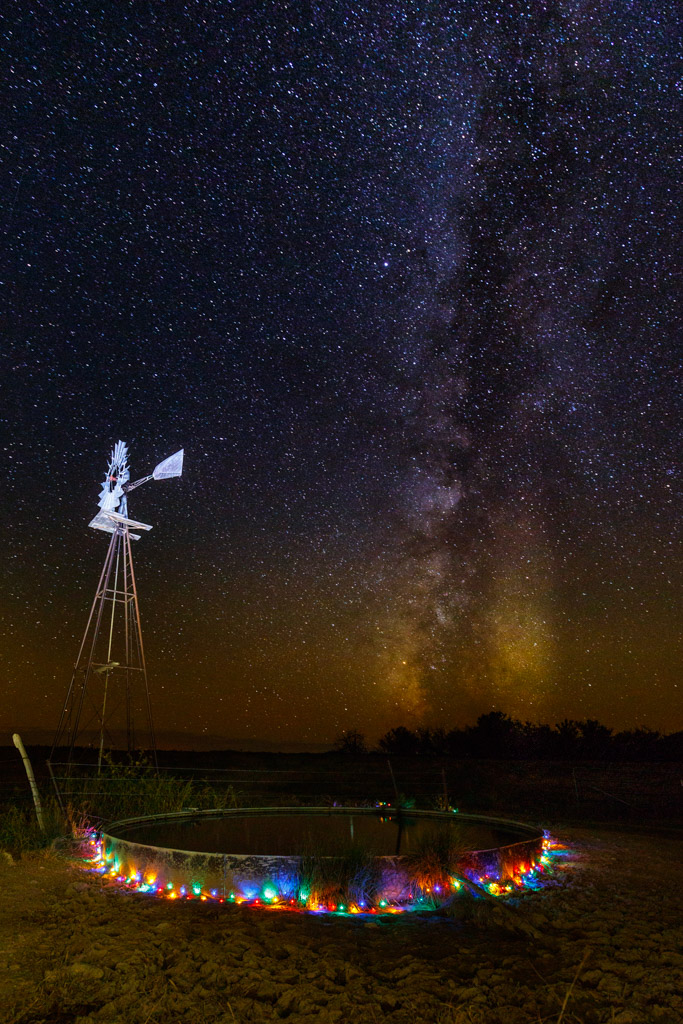 Windmill with holiday lights on stock tank beneath night stars and Milky Way, Rita Blanca National Grasslands, Texas, USA.