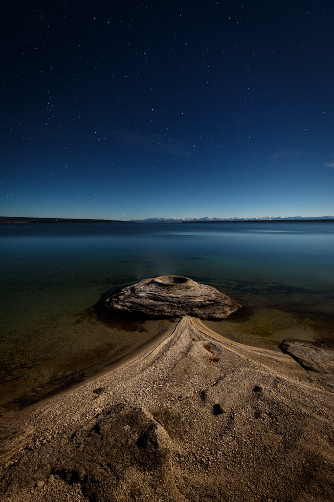 Fishing Cone and Night Stars, West Thumb Geyser Basin on shores of Lake Yellowstone, Yellowstone National Park, Wyoming, USA.