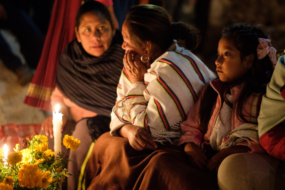 Women and girl during the Night of the Dead (Noche de Muerto) night-time vigil at cemetery on Isla de Janitzio as part of longer Day of the Dead festivities, Lake Pátzcuaro, Pátzcuaro, Michoacán de Ocampo, Mexico.
