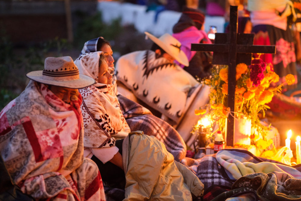 People bundled up during the Night of the Dead (Noche de Muerto) night-time vigil at cemetery on Isla de Janitzio as part of longer Day of the Dead festivities, Lake Pátzcuaro, Pátzcuaro, Michoacán de Ocampo, Mexico.